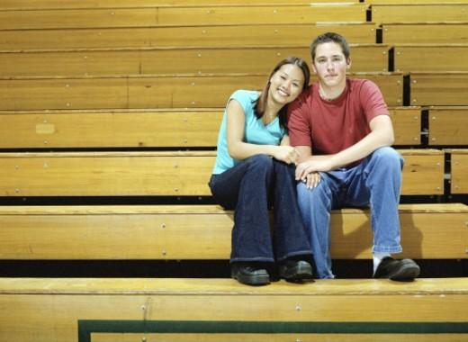 Teenage couple (15-17) sitting on school gym bleachers, portrait : Stock Photo