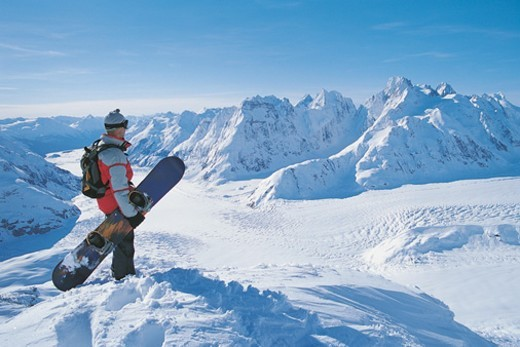 Stock Photo: 1527R-1187643 Side View of a Snowboarder Looking at the View of a Snow-covered Mountain Valley