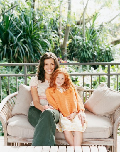Stock Photo: 1527R-1188614 Portrait of a Mother and a Daughter Sitting on a Sofa on Their Porch