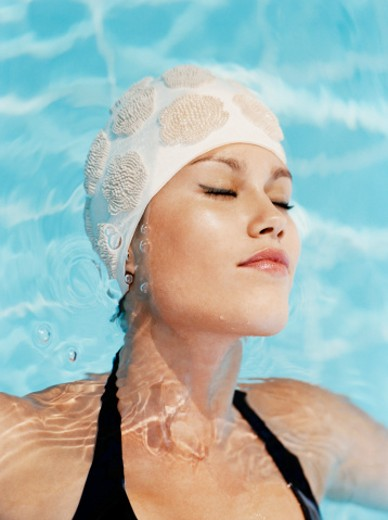 Young Woman Wearing a Swimming Cap and Floating in a Swimming Pool : Stock Photo