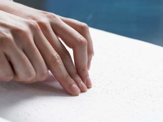 Close Up of a Hand Touching a Braille Book : Stock Photo