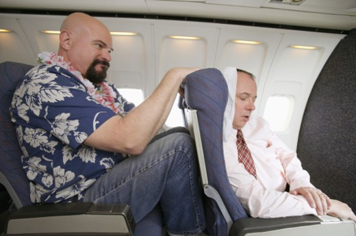 Stock Photo: 1527R-1189271 Passenger With His Knees Against a Sleeping Businessman's Chair on an Aeroplane