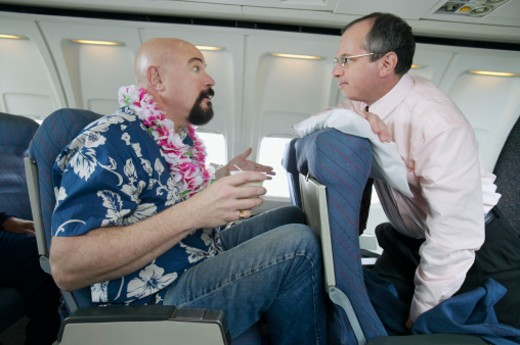 Passenger Angry About Seating Space on a Passenger Aeroplane : Stock Photo