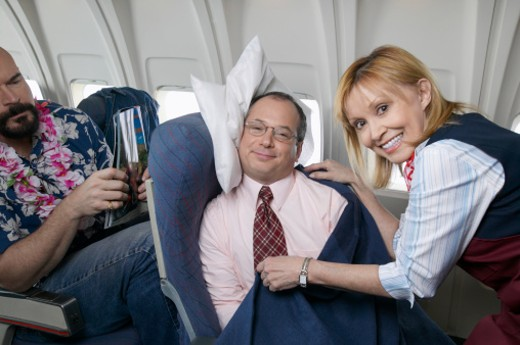 Stock Photo: 1527R-1189277 Air Stewardess Adjusting a Businessman's Blanket During a Flight