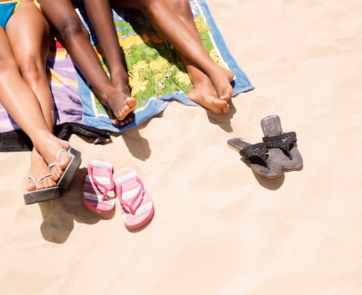 Low Section View of Three People Sunbathing on a Beach : Stock Photo