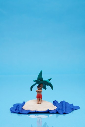 Clay model of man on desert island on blue background : Stock Photo