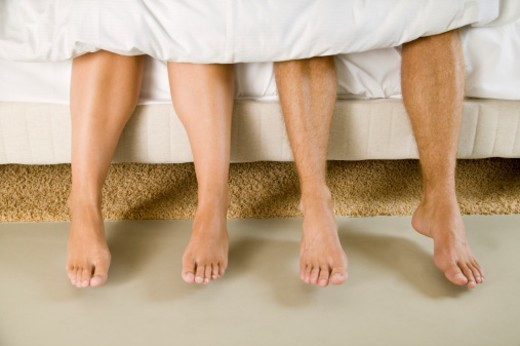 'Couple sitting on edge of bed, low section' : Stock Photo