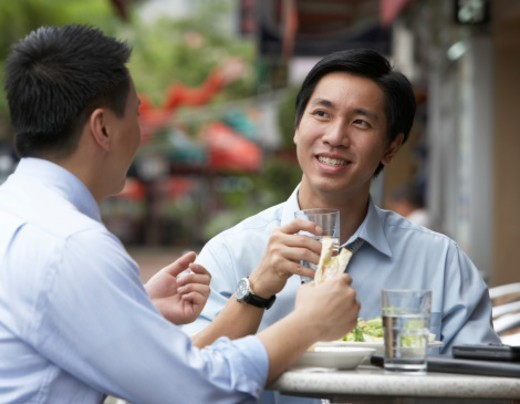 Two businessmen having lunch at outdoors cafe : Stock Photo