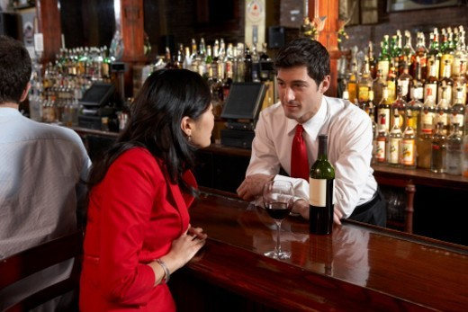 Stock Photo: 1527R-1190427 Woman talking to bartender in pub