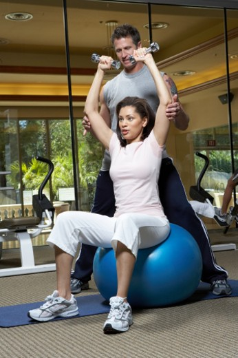 Male instructor helping woman in gym : Stock Photo