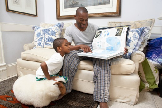Father and son (6-7) looking at colouring book on sofa : Stock Photo