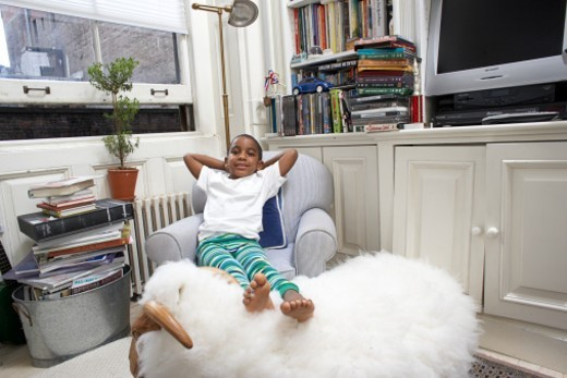 Stock Photo: 1527R-1191426 Boy (6-7) sitting on arm chair with legs on soft toy, portrait
