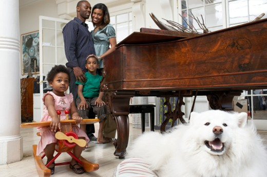 Stock Photo: 1527R-1191446 Girl (21-24 months) sitting on toy aeroplane, parents and brother (6-7) standing by piano