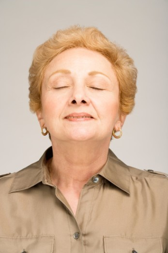 Senior woman with eyes closed, smiling, close-up : Stock Photo