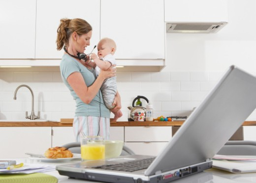 Mother holding baby boy ( 7-9 months) in kitchen : Stock Photo