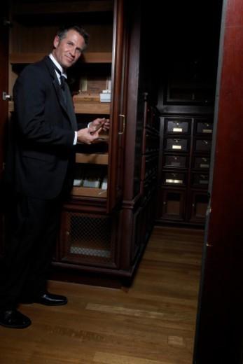 Man choosing cigar in humidor, full length : Stock Photo
