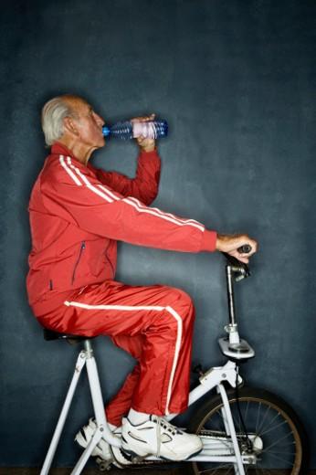 Stock Photo: 1527R-1192437 Senior man using exercise bike, drinking water, side view
