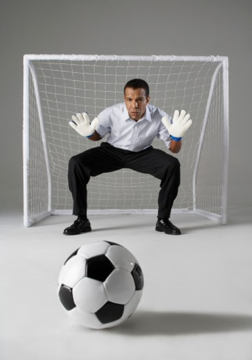Businessman playing goalkeeper, ready to block the ball, studio shot : Stock Photo