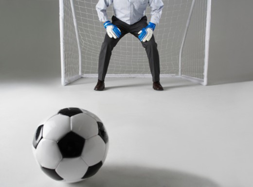 Stock Photo: 1527R-1193057 Business man playing goalkeeper, low section