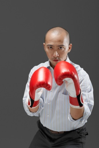 Businessman wearing boxing gloves, portrait : Stock Photo