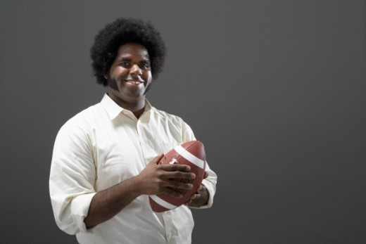 Man holding American football, portrait : Stock Photo