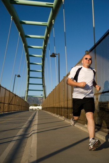 Stock Photo: 1527R-1193926 Man jogging on bridge