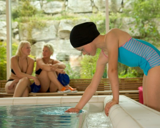 Girl (8-10) dipping hand in swimming pool, side view : Stock Photo