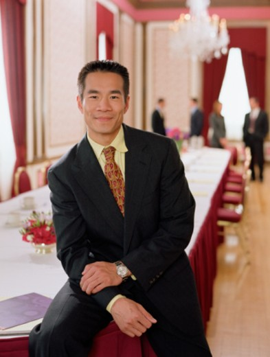 Businessman sitting on table in banquet room : Stock Photo