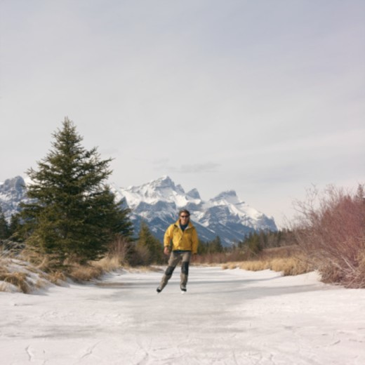 Canada, Alberta, Canmore, ice skater on frozen pond : Stock Photo