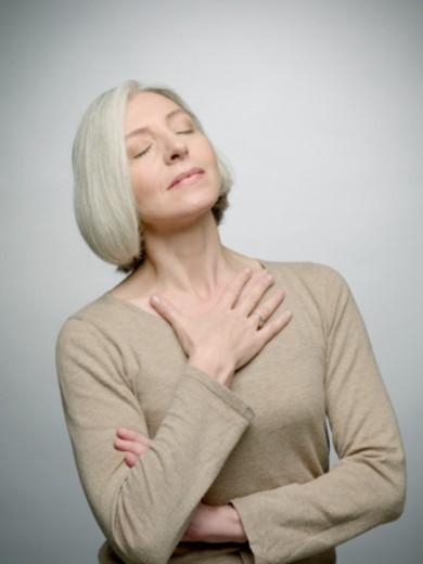 Mature woman with hand on chest, eyes closed : Stock Photo