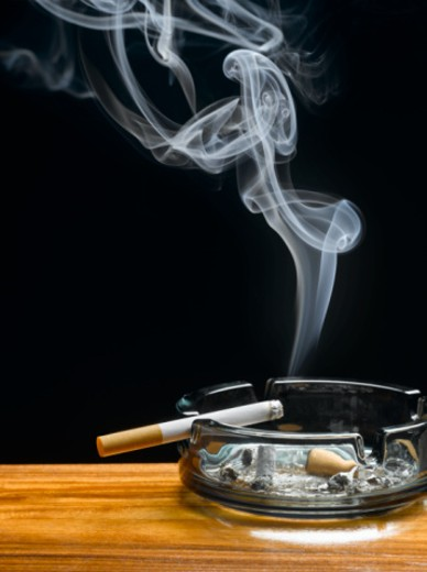 Stock Photo: 1527R-1196047 Burning cigarette in ashtray on table