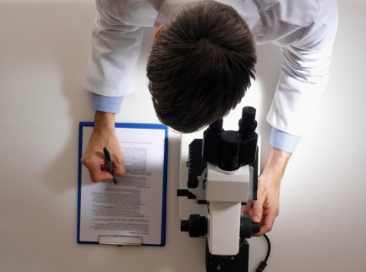 Man in white lab coat making notes by microscope, overhead view : Stock Photo