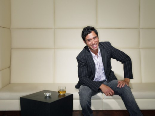 Young man with cocktail sitting in nightclub, laughing, portrait : Stock Photo