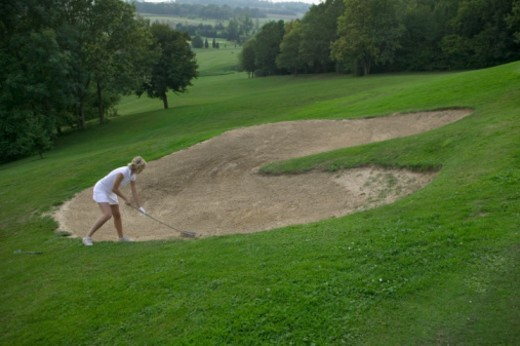 Stock Photo: 1527R-1197545 Female golfer taking shot from bunker