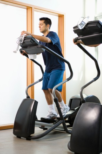 Young man working out on elliptical machine in gym : Stock Photo