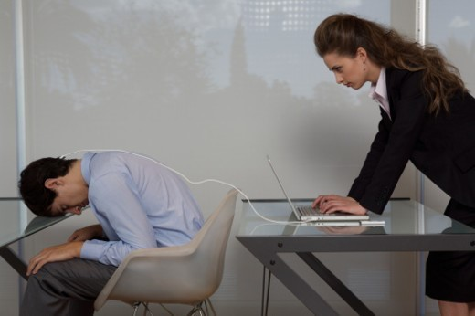 Businesswoman using laptop plugged into businessman's head, side view : Stock Photo