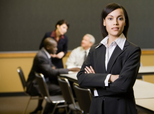 Four executives in conference room (focus on woman in foreground) : Stock Photo