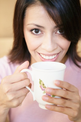 Young woman drinking coffee, portrait, close-up : Stock Photo