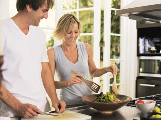 Couple in kitchen, woman tossing salad, smiling : Stock Photo