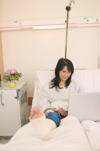 Female patient  in hospital bed using laptop computer : Stock Photo