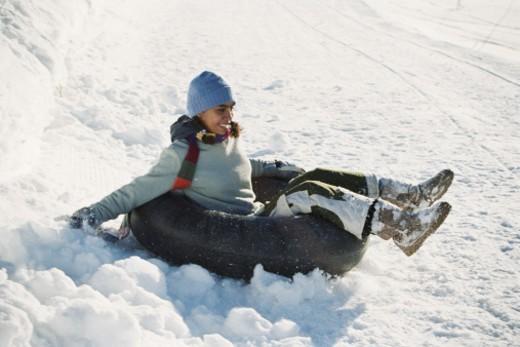 Stock Photo: 1527R-1199895 Teenage girl (13-15) riding inner tube down snow-covered hillside