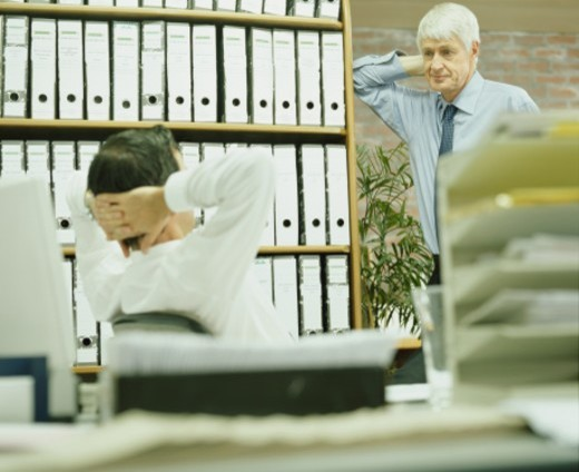 Stock Photo: 1527R-1200059 Two businessmen in office taking break (focus on man in background)