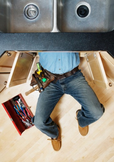Man lying beneath sink, making repair, low section, overhead view : Stock Photo