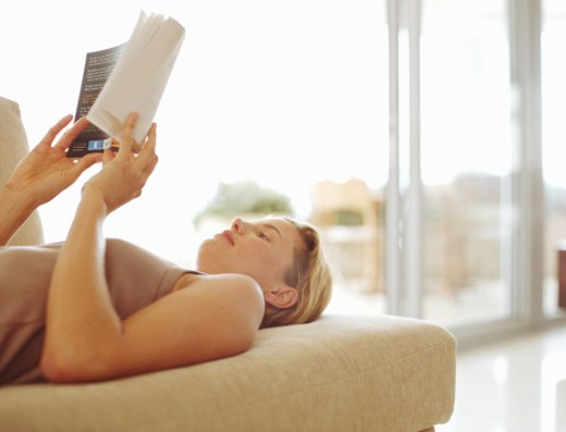 Young woman lying on sofa reading book (focus on woman's face) : Stock Photo