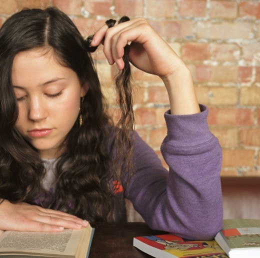 Stock Photo: 1527R-1200692 Teenage girl (15-17) reading while twirling her hair