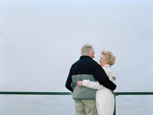 Stock Photo: 1527R-1200828 Senior couple standing by railing with arms around each other, smiling