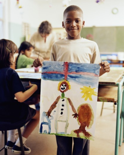 Boy (6-8) holding up painting in classroom, smiling, portrait : Stock Photo