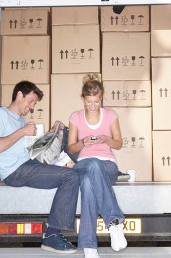 Couple in back of removal van, man reading paper, woman using mobile : Stock Photo