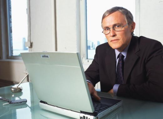 Mature businessman at desk with laptop, portrait : Stock Photo