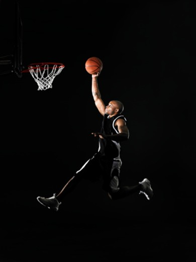 Young man jumping in mid air, preparing to dunk basketball, side view : Stock Photo